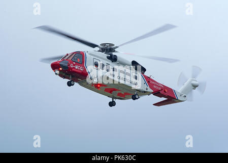 The Inverness based HM Coastguard SAR helicopter leaving its base as it heads West on a mission down to Fort William in Lochaber district. - Stock Image