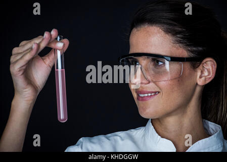 Young woman looking at liquid in test tube - Stock Image