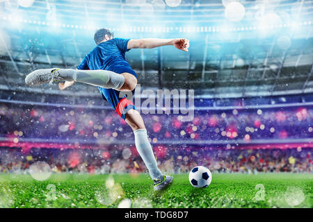 Football scene at night match with player kicking the ball with power. - Stock Image
