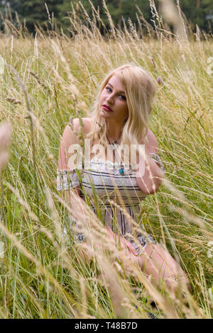 Beautiful young blonde woman enjoying nature in a field with high grasses - Stock Image