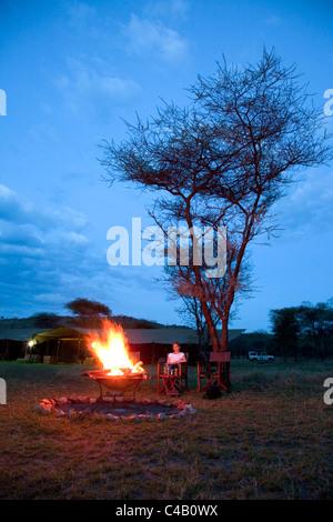 Tanzania, Serengeti. A tourist warmsup by the fire after a safari at Lemala Ewanjan. MR. - Stock Image