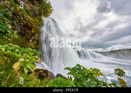 TUNGUFLJOT, ICELAND. 03 AUG 2016: Wide angle shot of Faxi waterfall with vegetation in the foreground and cloudy sky in the background. - Stock Image