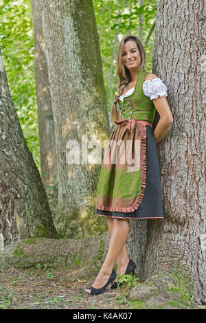 Woman In Green Dirndl Stands In The Forest Between The Mighty Tree Trunks - Stock Image