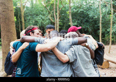 Men friends hugging in huddle on hike in woods - Stock Image