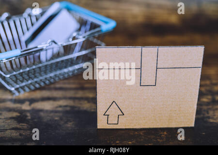 cardboard delivery parcel box on wooden desk with shopping basket and payment card in the background, concept of online purchases and shipping - Stock Image