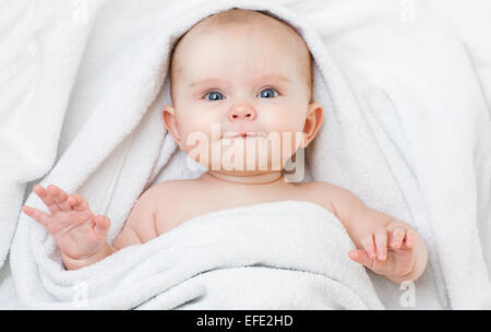 Cute funny smiling baby lying on back in bathing towel - Stock Image