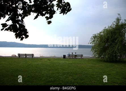 Three girls on a bench watch as a storm approaches over the Hudson River, Dobbs Ferry, NY, USA - Stock Image