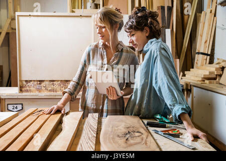 Two women choosing wood from a selection in a workshop, consulting on a tablet - Stock Image