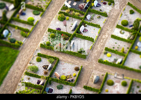 Cemetery with green hedges and gravestones decorated with flowers on a sunny day seen from above - Stock Image