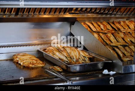 Traditional fishfilets being grilled to make sandwich served on the dock of Eminonu area of Istanbul. - Stock Image