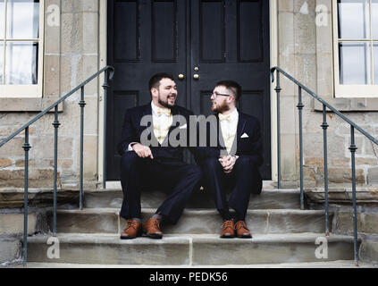 Two Men holding hands on steps - Stock Image