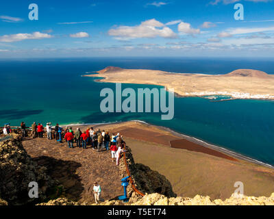 Tourists look across to the island of La Graciosa from the Mirador del Rio viewpoint on Lanzarote Canary Islands - Stock Image