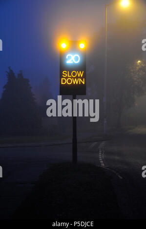 A traffic sign showing the speed limit on a foggy night. - Stock Image