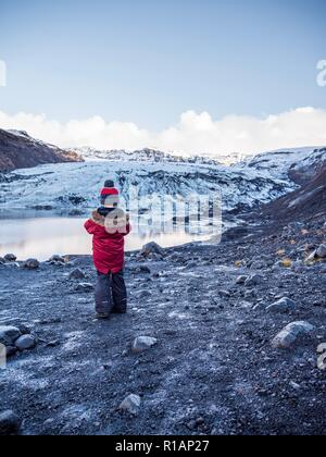 A little boy stood staring at the mouth of a glacier in southern Iceland - Stock Image