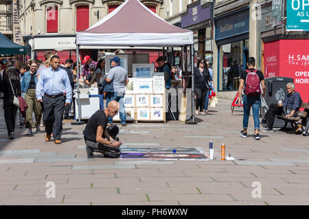 Street artist drawing with pastel on paper fixed to the pavement in Union Street in the city of Bath - Stock Image