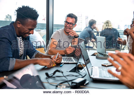 Colleagues using laptops during meeting - Stock Image