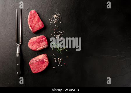Raw sirloin beef steaks with salt, pepper, rosemary, and a carving fork on a black background with a place for text - Stock Image