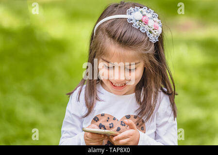 Adorable four years old cute little girl in casual clothes holds and texts mobile phone while smiling at outdoor in park - Stock Image
