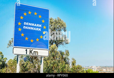 Road sign on the border of a European Union country, Denmark 1km ahead with blue sky copy space. - Stock Image