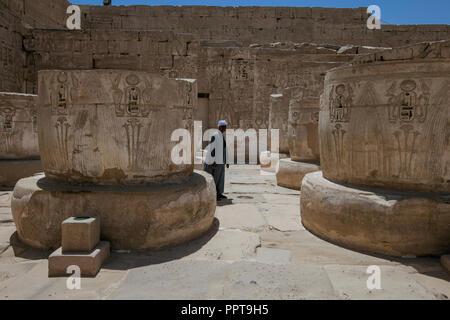 Egyptian man walking across courtyard of cut-off columns in Medinet Habu Temple of Ramses III in Luxor, Egypt. - Stock Image