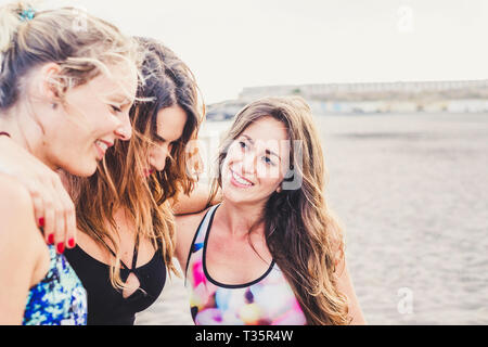 Group of young beautiful women friends hug and enjoy the friendship together in outdoor beach - tourism and sport activity for healthy people - caucas - Stock Image
