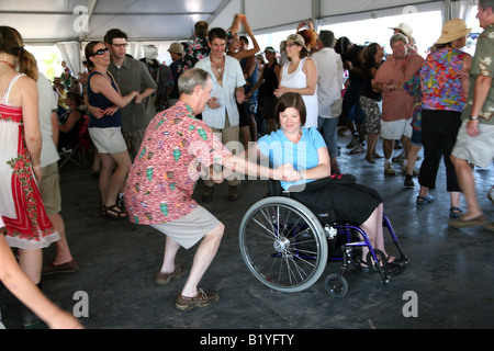Woman in a wheelchair dancing at the Economy Hall tent at the New Orleans Jazz and Heritage Festival, New Orleans, - Stock Image