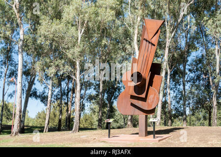 A Corten Steel Picasso Guitar sculpture by Peter Hooper in 2016 on display in Tamworth Bicentennial Park NSW  Australia. - Stock Image