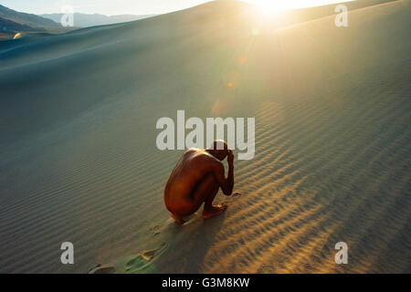 Nude woman cowering in desert - Stock Image