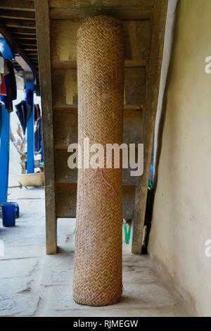 Rolled straw braided mat stored on the porch of a guesthouse in the Annapurna region, Nepal. - Stock Image