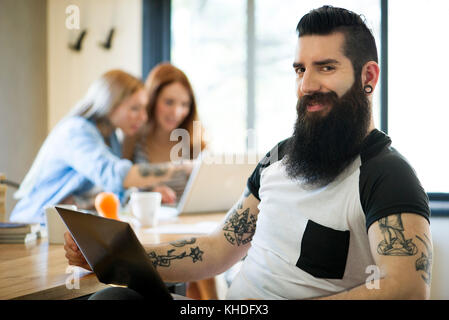 Man using laptop computer, smiling, portrait - Stock Image