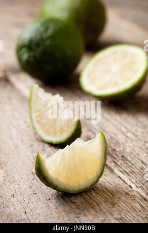 Lime slices on wooden background close-up - Stock Image