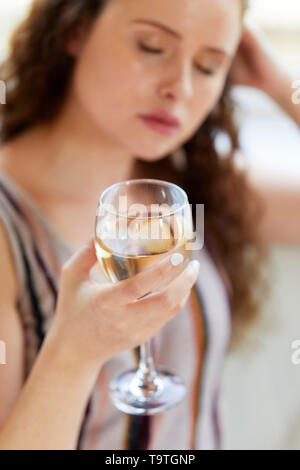 Woman drinking glass of wine - Stock Image