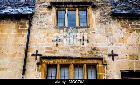 Cotswold limestone is kept in place by four tie plates on the facade of this terraced cottage in the market town high street of Chipping Campden - Stock Image