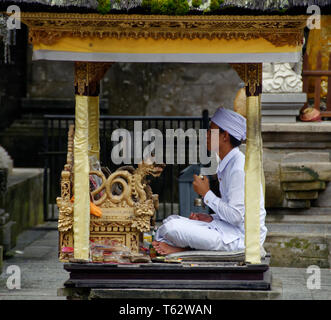 Prayer leader in a small cabin, Pura Tirta Empul temple, Ubud, Indonesia - Stock Image
