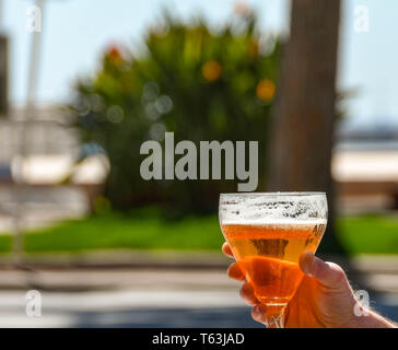 CANNES, FANCE - SEPTEMBER 2018: Person holding up a glass of golden lager beer at a seafront cafe in Cannes. The glass is backlit with sunlight. - Stock Image