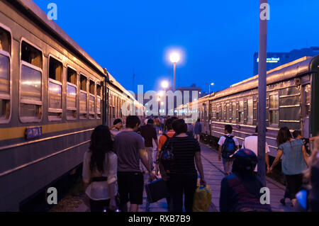 Passengers on a platform with trains either side at Hanoi railway station (Ga Hà Nội) in early morning, Hanoi, Vietnam - Stock Image