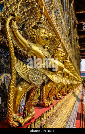 Golden statues in the Grand Palace in Bangkok, Thailand - Stock Image