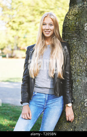 young woman with long blond hair and leather jacket leaning against tree in a park on a sunny day in spring - Stock Image