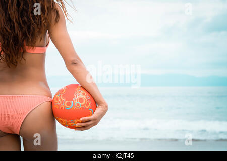 Woman beach fitness - back side of attractive female holding beach volleyball, Riviera Nayarit, Mexico - Stock Image