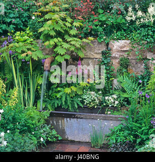 Detail of a garden with a floral decorative water supply - Stock Image