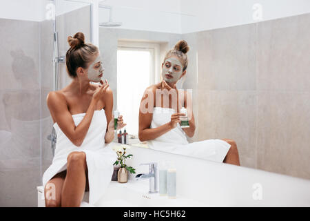 Young woman applying facial mud clay mask to her face in bathroom. Beautiful female wrapped in towel looking into - Stock Image