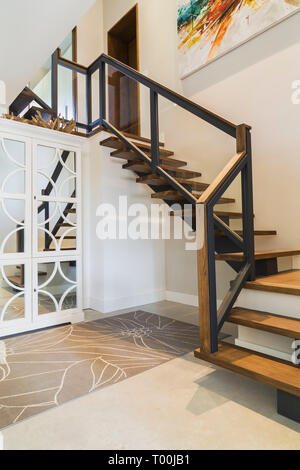 Hickory wood stairs with black metal and wood top clear glass railing leading from basement room to main floor inside luxurious contemporary home - Stock Image