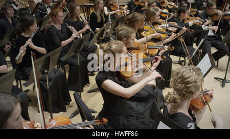 High angle view of student musicians playing instruments in orchestra recital - Stock Image