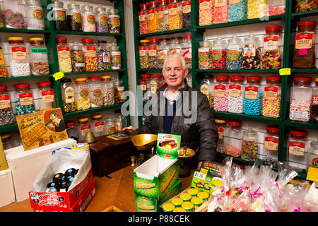 UK, Northern Ireland, Co Antrim, Carrickfergus, North Street, owner Allan Millar in Millar's Old Time Sweet shop - Stock Image