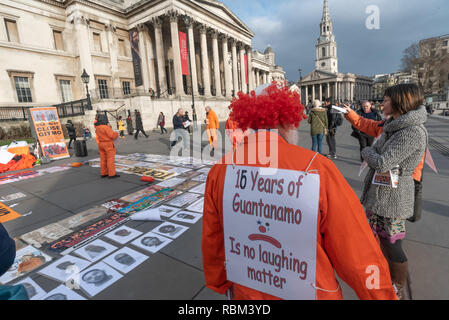 London, UK. 11th January 2019. A man in a clown headdress has the message on his back '16 years of Guantanamo Is no laughing matter' at the protest  by the Guantanamo Justice Campaign and London Guantanamo Campaign marking the 17th anniversary of the first prisoners arriving at the illegal US camp. A display of posters, photographs of the remaining detainees, readings and speeches in Trafalgar Square highlighted the abuse, torture, lack of human rights, force-feeding and indefinite detention there. Credit: Peter Marshall/Alamy Live News - Stock Image