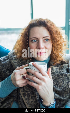 Woman with red, curly hair sitting with a mug by a window; Surrey, British Columbia, Canada - Stock Image