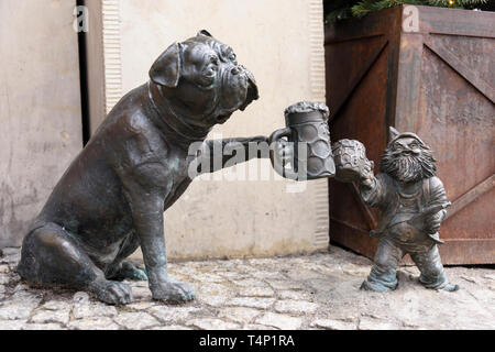 One of the brass gnomes (krasnale, krasnoludki) having a drink of beer with a bulldog dog, Wrocław, Wroklaw, Poland - Stock Image