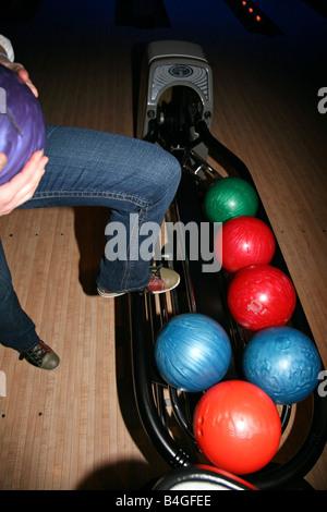 Woman's leg stepping on bowling ball rack - Stock Image