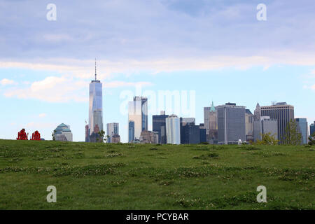 Couple sitting on two red garden chairs on Governors Island Hills watching Financial District skyline, Governors Island on JULY 4th, 2017 in New York, - Stock Image
