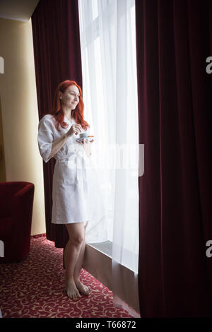 A ginger woman standing by the window and looking at the streets - Stock Image
